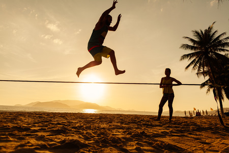 teenagers balance slackline on sunrise beach silhouette Stock Photo