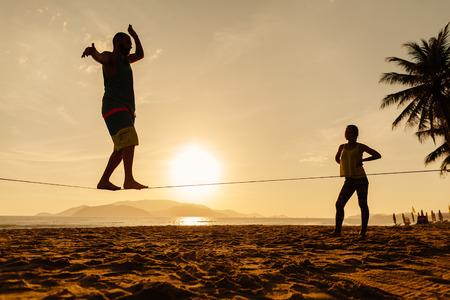 freedom nature: teenagers balance slackline on sunrise beach silhouette Stock Photo