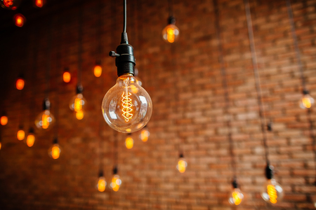 light interior: light bulb Edison  filament retro vintage decore on brick wall background. Lighting decoration
