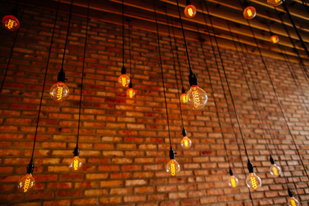 white light: light bulb Edison  filament retro vintage decore on brick wall background. Lighting decoration