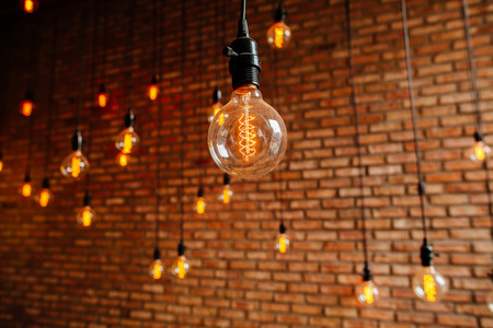 decore: light bulb Edison  filament retro vintage decore on brick wall background. Lighting decoration