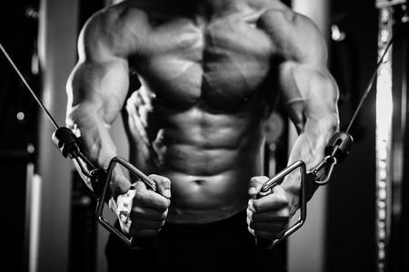 bodybuilder: chico culturista en el bombeo de gimnasio hasta las manos de cerca. En blanco y negro