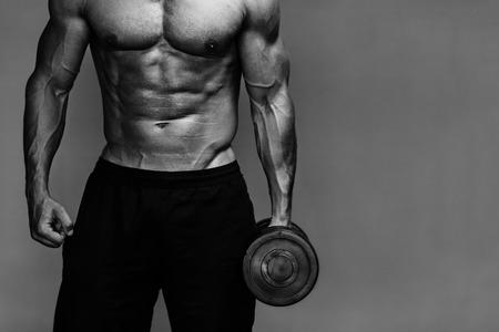 deportista: Cierre para arriba del individuo culturista musculoso haciendo ejercicios con pesas sobre fondo gris. En blanco y negro