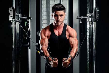 hombre deportista: apuesto culturista funciona empujando hacia arriba ejercicio en el gimnasio