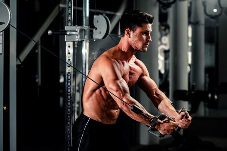 culturista: apuesto culturista funciona empujando hacia arriba ejercicio en el gimnasio