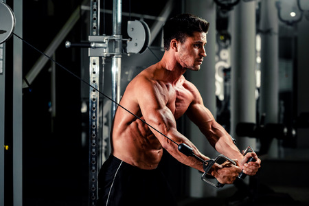 bodybuilding: handsome bodybuilder works out  pushing up excercise in gym Stock Photo