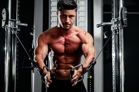 bodybuilder: apuesto culturista funciona empujando hacia arriba ejercicio en el gimnasio
