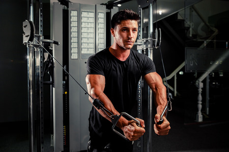 excercise: handsome bodybuilder works out  pushing up excercise in gym Stock Photo