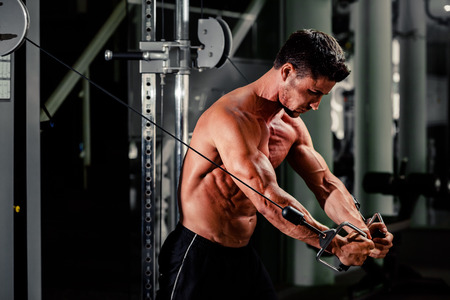 kettlebell: handsome bodybuilder works out  pushing up excercise in gym Stock Photo