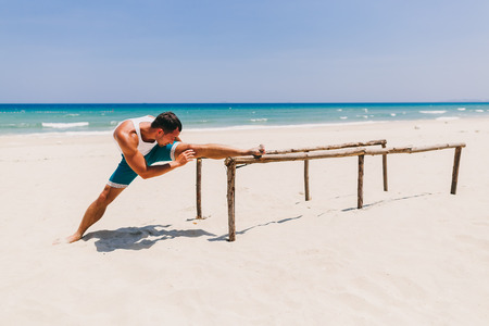 man stretching and doing gymnastic on the beach