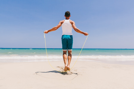 fitness man skipping on the ocean freedom beach with blue sky back view Stock Photo