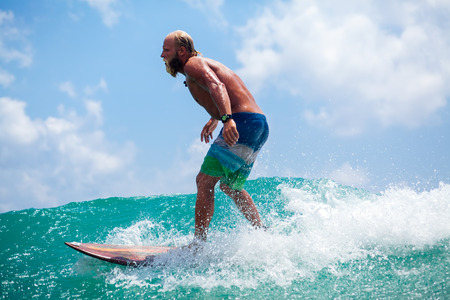 man with beard surfing wave splash actively