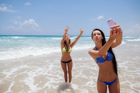 niñas en bikini: dos felices sexy girls selfie teléfono inteligente en la playa Foto de archivo