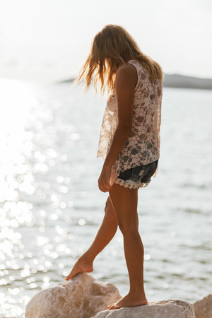 breeze: dreamy girl on beach with sea view and light breeze wind in hair. back view