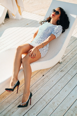 long legged: fashion luxury brunette long  legged  lady model portrait with red lips and sunglasses on white sunbed