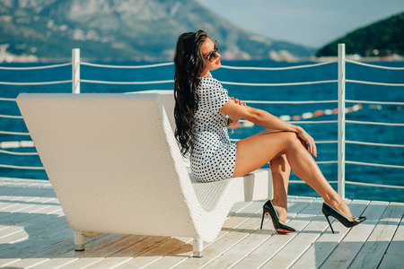 chill out: fashion luxury brunette lady model on beach chill out white sunbed Stock Photo