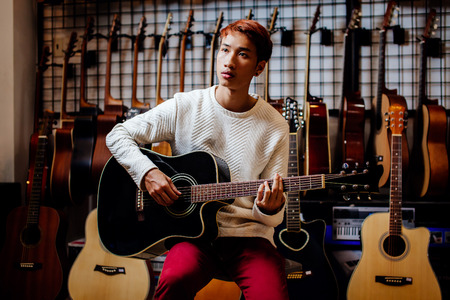 handsome asian teenage man playing acoustic guitar in guitar shop