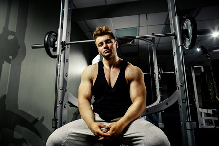 tank top: strong bodybuilder handsome athlete in black tank top with high weights in gym Stock Photo