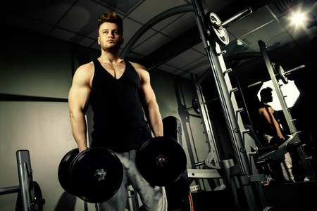 strong handsome bodybuilder athlete works out and pumping with heavy  dumbbells in gym