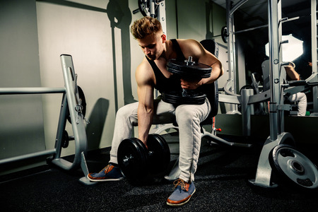 the athlete: strong handsome bodybuilder athlete works out and pumping with heavy  dumbbells in gym