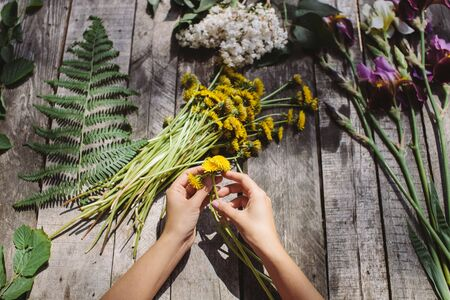 flower decoration of dandelions and irise lilac flowers handmade on vintage wood table Stock Photo