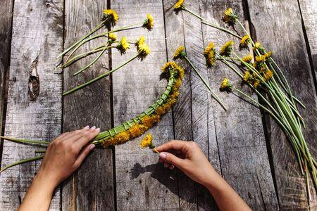 circlet: wreath of dandelions flowers handmade handicraft with flowers on vintage wood table Stock Photo
