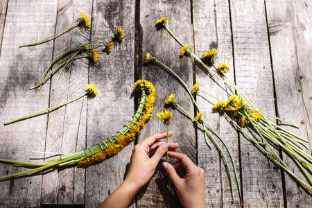 wreath of dandelions flowers handmade handicraft with flowers on vintage wood table Stock Photo