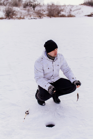 jig: winter fisherman with jig and fish on frozen lake