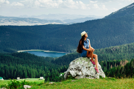 long hair woman relax on peak of mountain landscape with picturesque view in Montenegro, Durmitor