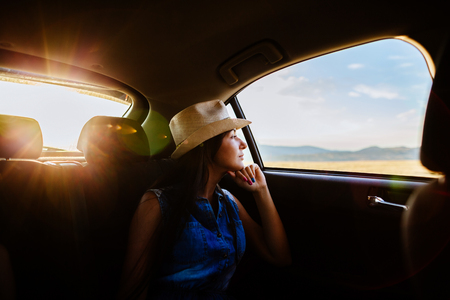 cowboy: woman travel and dreaming by car in cowboy hat with sunlight in mountains