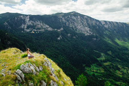 views of the mountains: woman yoga relax at the end of earth in fascinating landscape in Montenegro