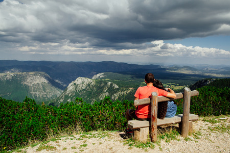 lovely couple relax on peak of mountains on wooden bench with fascinating picturesque landscape view and rainy sky in Montenegro, back view