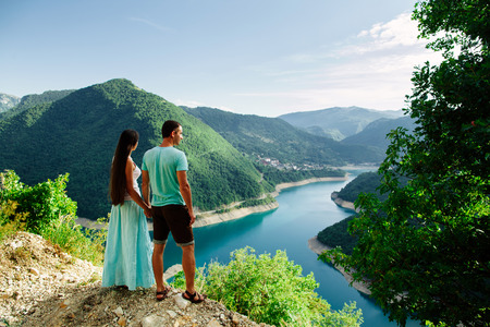 lovely couple relax on peak of mountains with fascinating picturesque landscape view in Montenegro