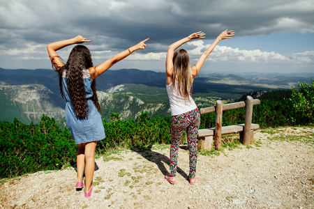 women friendship: two long hair girls happy dnce on peak of mountains with exciting view of Montenegro, back view