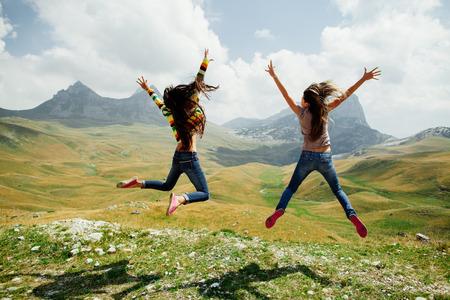 jumping: dos chicas de pelo largo salto feliz en las montañas con vistas atractivas de Montenegro, Durmitor, vista posterior