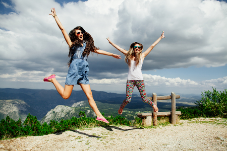hooray: two long hair girls happy jump in mountains with exciting view of Montenegro, back view