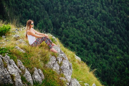 fascinating: blonde woman in sunglesses sit and relax at the end of earth in fascinating landscape in Montenegro