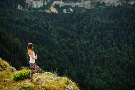 mountains and sky: woman yoga relax at the end of earth in fascinating landscape in Montenegro