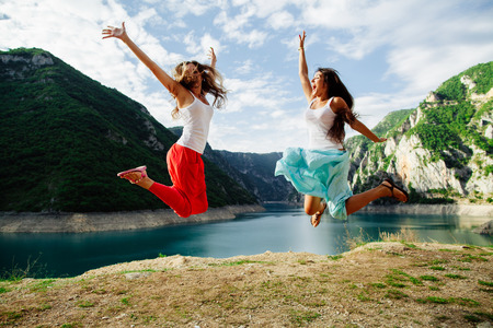 hooray: two long hair girls happy jump in mountains with exciting view of Montenegro