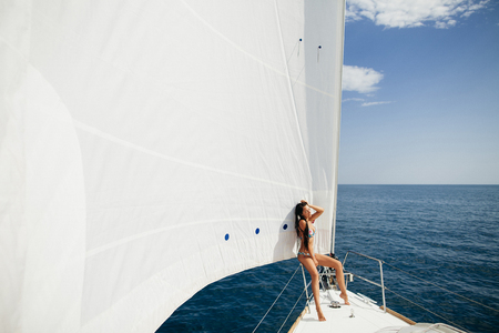 yacht people: sexy girl in swimwear on yacht under big white sail