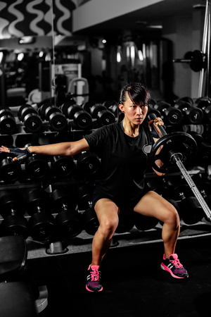 asian sexy fitness girl  weightlifting in gym with heavy weights on black background
