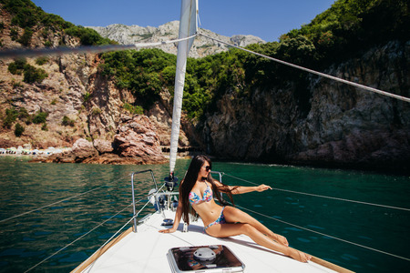 recreation yachts: sexy long hair girl in swimwear on yacht in Montenegro Stock Photo