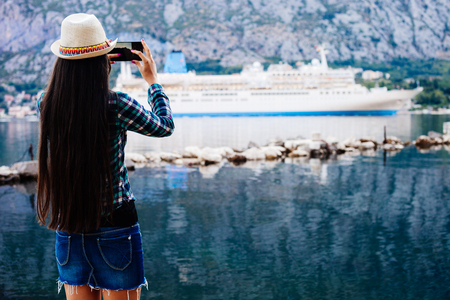 cruise liner: girl taking photo on smartphone of cruise liner yacht in picturesque landscape bay water bakground view