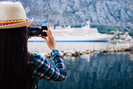 cruise liner: girl taking photo on smartphone of cruise liner yacht