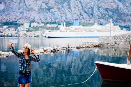 cruise liner: girl taking selfie photo on smartphone of cruise liner yacht in picturesque landscape bay water bakground view