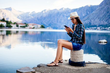 girl travel and search in smartphone on beach of bay
