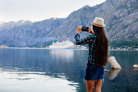 cruise liner: girl taking photo on smartphone of cruise liner