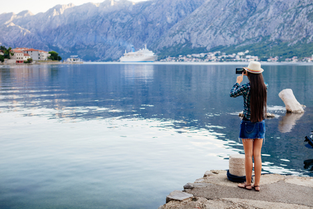 cruise liner: girl taking photo on smartphone of cruise liner yacht in Montenegro Stock Photo