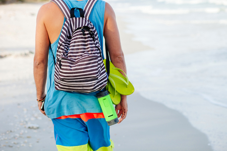 thongs: backpacker man travel with thongs and music player on beach in tropics backview