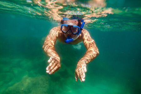picada: bucear hombre nadar bajo el agua en el mar turquesa